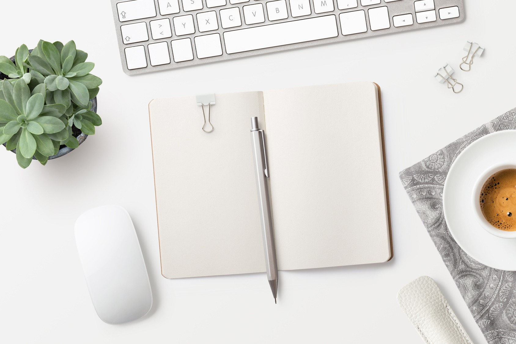 Desktop with blank open notebook, coffee, office supplies and succulents on a white table